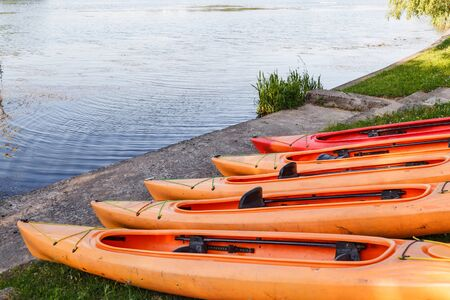 Polymer kayaks, water sports. Canoe summer club equipment. Active rest, sport, kayak. Boat for rafting on water. A few kayaks stand on rent point. Reklamní fotografie