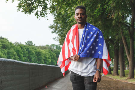 Handsome Afro American man with USA flag on his shoulders seriously looking at camera, standing outdoors. Day summer