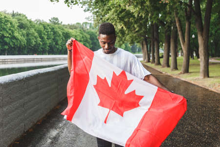 Handsome Afro American man with Canadian flag, standing outdoors. Reklamní fotografie