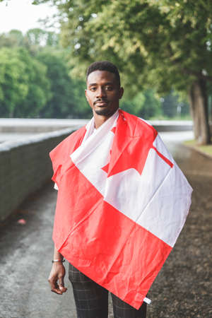 Handsome Afro American man with Canadian flag on his shoulders seriously looking at camera, standing outdoors.
