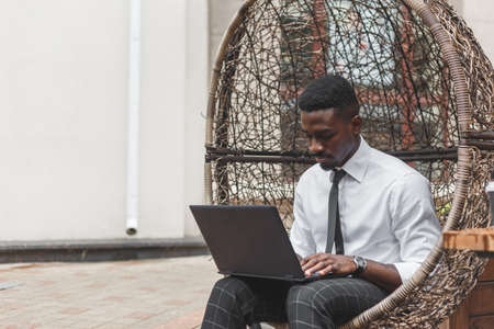 African business man working on laptop in outdoors cafe sitting in the egg chair. Reklamní fotografie