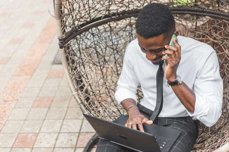 Cheerful young African man in formal wear talking on the mobile phone and working on laptop while sitting on egg chair at outdoors cafe