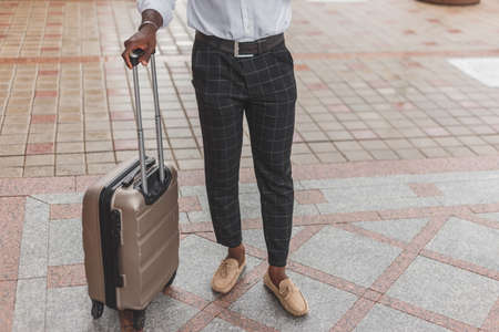 Stylishly dressed black guy with luggage standing outdoors. Reklamní fotografie