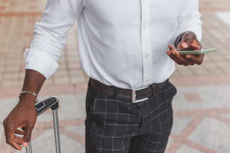 Black man with luggage bag standing on city street using smartphone, wearing formal style clothes.