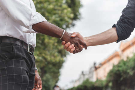 Handshake between african and a caucasian man outdoors.
