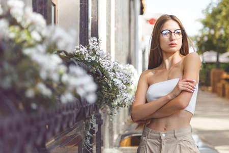 Young fashionable girl wearing eyeglasses, top, posing in street of European city. Copy, empty space for text