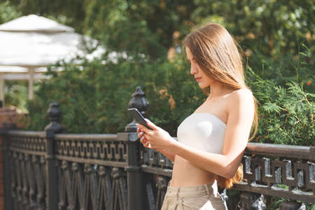Young stylish pretty woman with smartphone in the city streets.