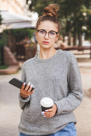 Young girl dressed in casual clothes with smartphone and a cup of takeaway coffee. Daily life of youth. People online