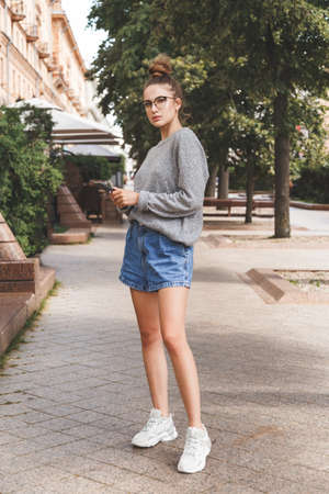 Young girl dressed in casual clothes with smartphone. Daily life of youth. People online.