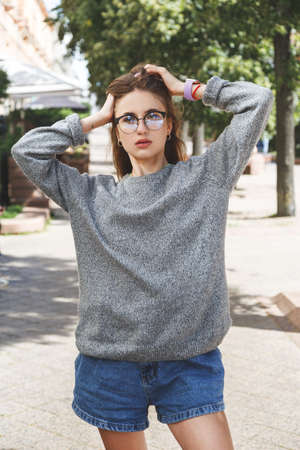 Young woman in gray sweater and denim shorts in the street. Reklamní fotografie