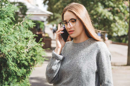 Fashion girl in eyeglasses on the street calling on mobile phone.