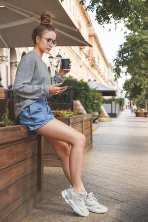 Young stylish pretty woman with smartphone and take away paper cup Reklamní fotografie