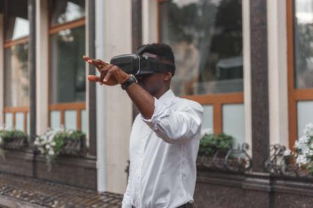 African businessman use virtual reality glasses on the street. VR headset Reklamní fotografie