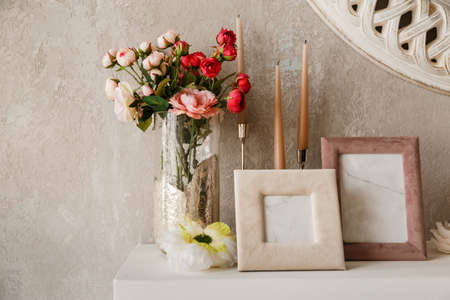 Vintage blank wooden frames and rose in a vase on a white shelf
