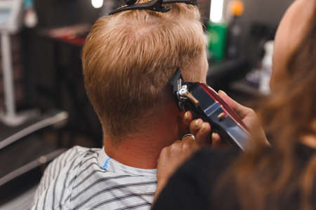Female barber in mask cuts a man hairs with hair clipper. hairstyle during social distancing Imagens