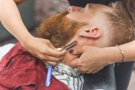 Barber woman shaves beard with a straight razor. Hairdresser equipment. Selective focus. Master in face mask 版權商用圖片