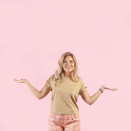 Caucasian blonde woman smiles and spreads her hands gesturing no idea isolated on pink background.