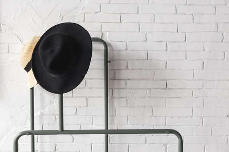 Black and white hat on hanger. White brick wall