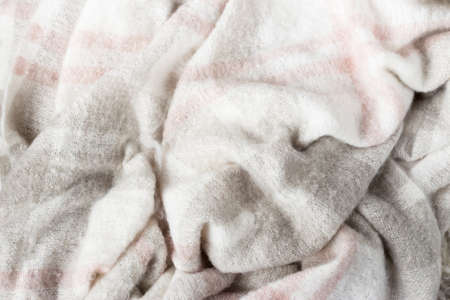 Crumpled gray wool blanket. Soft and warm fabric crumpled in folds. Autumn or winter vibe texture Stock Photo