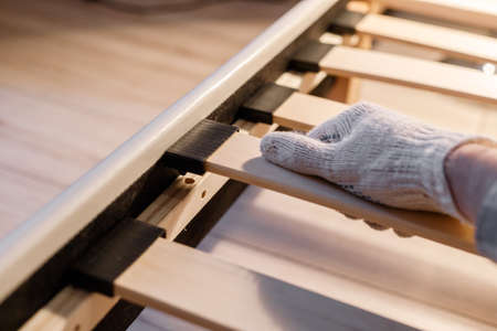 Male workers hand in glove assembling bed, connecting slats to bed frame