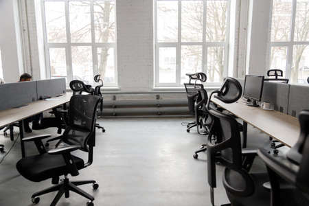 Interior of modern coworking space without people, containing tables and chairs