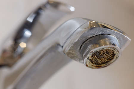 Limescale on faucet mesh in bathrooms. Close up view