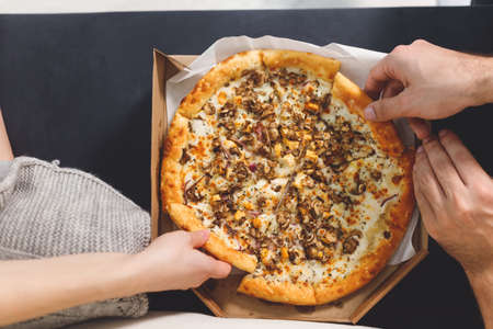 young couple eating pizza. Top view hands with pizza