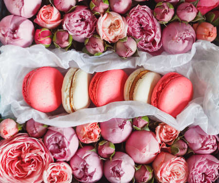French macaron cake. Macaroons in box with fresh flowers. Top view.