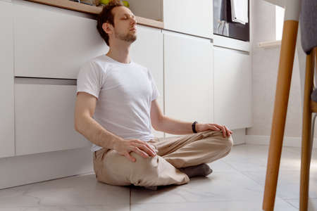 Young man meditating in home kitchen on floor sitting in the lotus position with closed eyes
