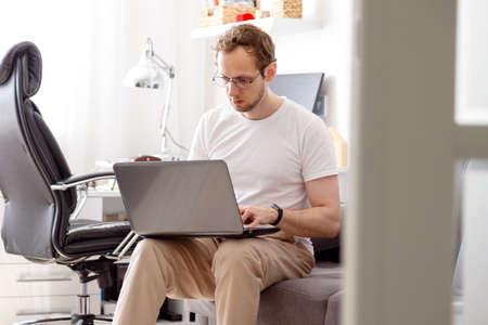 Young man with beard, working at home in living room sitting on coach with his laptop in front of him. Standard-Bild