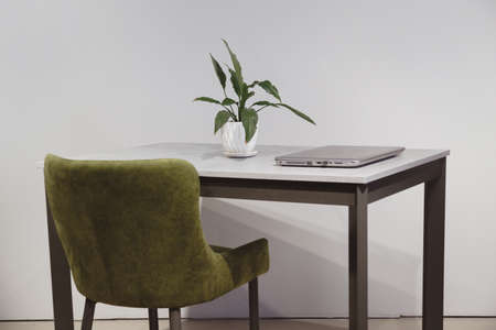 Modern minimalist workplace. Green velours armchair and loft table with laptop