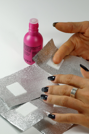 The procedure for varnish from nails (hybrid varnish) in progres. A womans hand with foils. Stock Photo