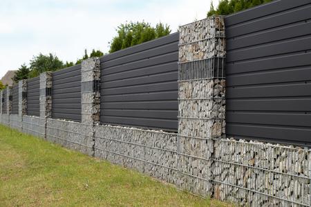 Nowoczesna forma ogrodzenia domu. Gabiony, siatki stalowe ocynkowane wypełnione łupanym kamieniem