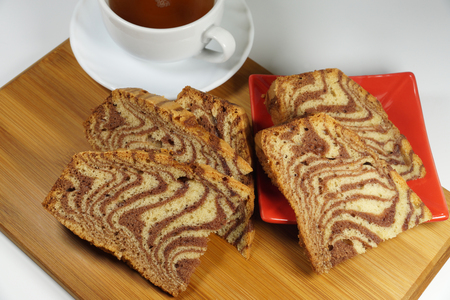 Zebra type cake, tea, red saucer and cutting board