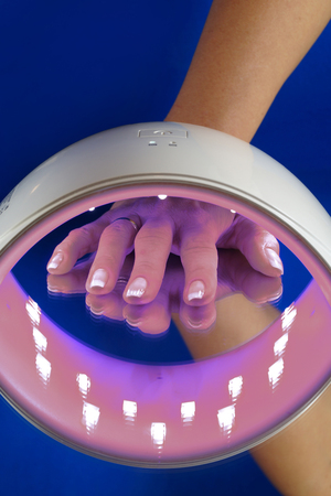 Steps to harden the hybrid nail polish. A hand of a woman under a UV lamp, curing hybrid varnish. Stock Photo