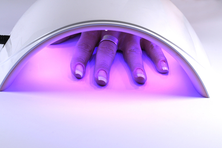 Manicure with uv led lamp, curing gel or hybrid varnish, manicure on table. Hand of a woman under the lamp Stock Photo
