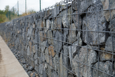 Close-up of a retaining wall made of stones. A wall called a gabion. Stock Photo