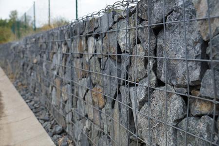 Close-up van een keermuur gemaakt van stenen. Een muur die een schanskorf wordt genoemd.