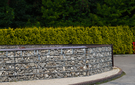 Arrangement of space made with the help of a fence made of stones placed in steel baskets. Gabion.