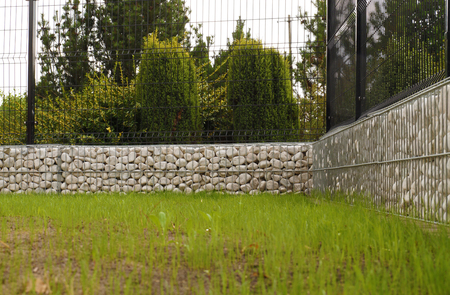 The fence is made of gabions filled with white pebbles