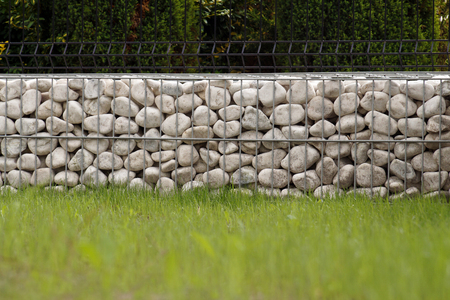 Impressive way of fencing the garden, metal baskets filled with white pebbles.