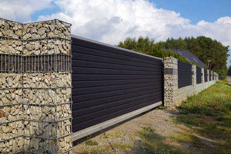 The entrance gate and a very long fence of the house using gabions.