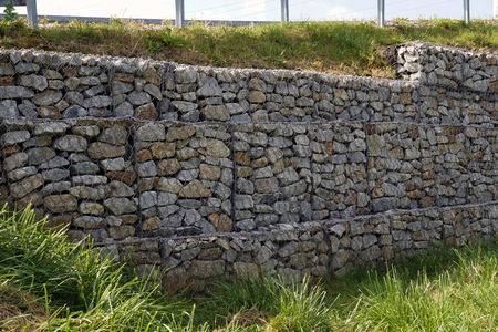 A fragment of a retaining wall made of gabions. Strengthening the steep slope. Stock Photo
