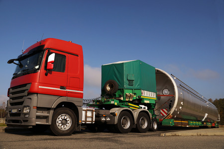 View of a red truck, low-loader semi-trailer and oversized load. Stock Photo