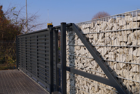 Automatic entrance gate used in combination with a wall made of gabion. Stockfoto
