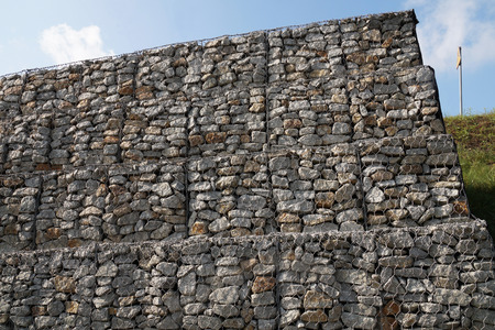 A fragment of the retaining wall of the road made of gabions. Strengthening the steep slope. 스톡 콘텐츠