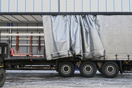 Transport en lossen. Een oplegger met een zichtbaar dekzeil tijdens het lossen.