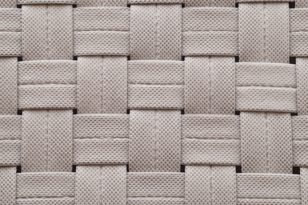Nonwoven strips interlaced with the simplest weave. Background.