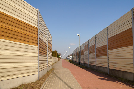 Protective walls, acoustic panels. A housing estate protected against noise from the street using sound-absorbing barriers. Stock Photo