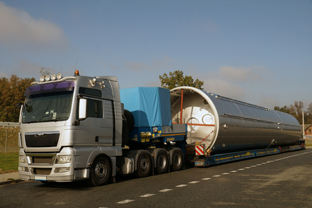 View of a silver truck, low-loader semi-trailer and oversized load.